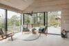 Moderne trævilla med vinduer i hjørnet af stuen. Vinduerne springer i øjnene med deres sortmalede ramme.
